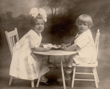 MIG - Marian Irwin and her brother Homer at a table @1919