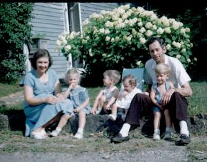 APG & MIG - whole family sitting next to driveway - summer - 1949